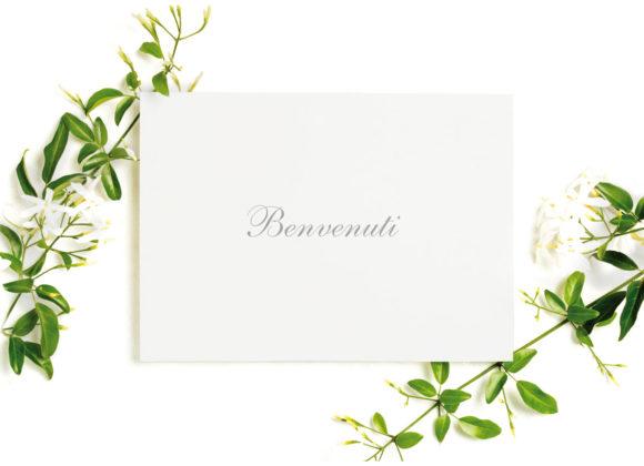 un biglietto con scritto benvenuti contornato da fiori